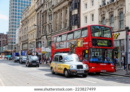 LONDON - JULY 1, 2014: Double-decker red bus and a black cab at a bus stop on Oxford street in London near Tottenham Court Road Station and Central Point. - stock photo