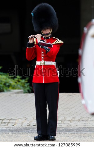 LONDON - JULY 4: Female member of Marching Band in front of Wellington Barracks on July 4, 2012 in London. Women are not permitted to serve in combat units In the British Armed Forces. - stock photo