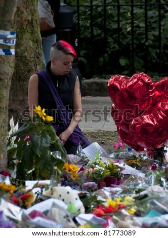 LONDON - JULY 27: Her fans pay tribute to Amy Winehouse in front of her house on Camden square, on July 27, 2011 in London. Amy Winehouse died aged 27 on Saturday, July 23. - stock photo