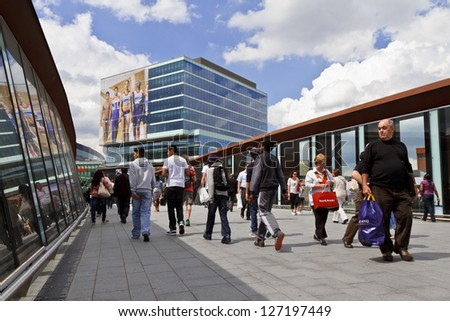 LONDON - JULY 5: People cross footbridge to Westfield Stratford City shopping centre on July 5, 2012 in London. It is the 3rd largest shopping centre in the United Kingdom. - stock photo