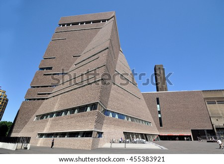 LONDON - JULY 19, 2016. The angular perforated brickwork of the Tate Modern art gallery extension designed by Herzog & de Meuron filters daylight in and emits artificial light, at Bankside, London. - stock photo