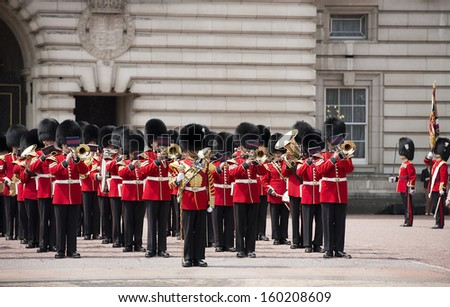 LONDON - JULY 12: the colorful changing of the royal guard ceremony at Buckingham Palace on July 12, 2013 in London, which is one of England's most popular visitor attractions. - stock photo