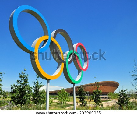 LONDON - JULY 3. The Olympic Games symbol and Velodrome cycle arena in the new Queen Elizabeth Olympic Park, on July 3, 2014, a legacy of the games at Stratford, east London, UK. - stock photo