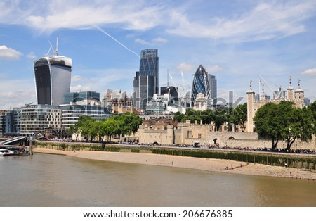 LONDON - JULY 16. The View from the south bank, across the River Thames with the skyscrapers dominating the Financial District skyline and the Tower of London on July 16, 2014 in London, UK. - stock photo