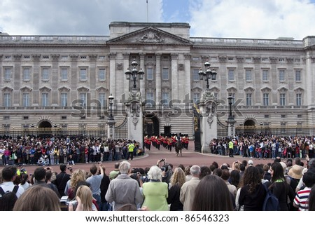 LONDON - JULY 29: Tourists watch changing the Royal Guards in the Buckingham Palace on July 29, 2007 in London, Great Britain - stock photo
