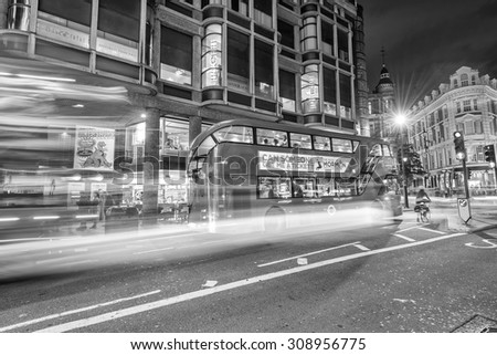 LONDON - JUNE 11, 2015: Black and white vintage traffic scene near Piccadilly Circus. The city attracts 50 million people annually. - stock photo