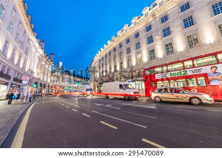 LONDON - JUNE 15, 2015: Buses and traffic in Regent Street at night. London attracts 50 million people across the world. - stock photo