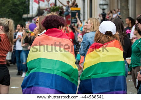 LONDON, JUNE 25, 2016: LGBT Gay Pride Parade Two Woman Wrapped In Rainbow Flags - stock photo