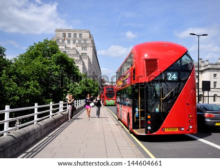 LONDON - JUNE 29. London's new diesel-electric hybrid Routemaster double deck bus with three doorways and two staircases accommodates 80 passengers, June 29, 2013, on Waterloo Bridge, London, UK. - stock photo