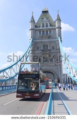 LONDON - JUNE 01, 2014: open top London Bus travels across the Tower Bridge in London. The Tower Bridge is a suspension bridge with a total length of 244 metres.