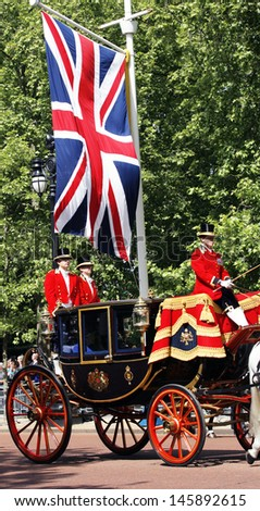 LONDON - JUNE 15: Queen Elizabeth II seat on the Royal Coach at Queen's Birthday Parade on June 15, 2013 in London, UK. Queen's Birthday Parade take place in every June in London.   - stock photo