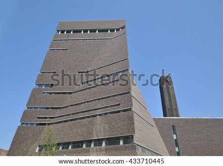 LONDON - JUNE 6, 2016. The angular perforated brickwork of the Tate Modern art gallery extension designed by Herzog & de Meuron filters daylight in and emits artificial light out, at Bankside, London. - stock photo