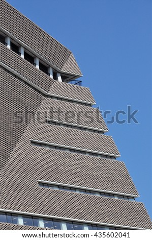 LONDON - JUNE 6, 2016. The angular perforated brickwork of the Tate Modern art gallery extension, designed by Herzog & de Meuron, filters daylight in and emits artificial light, at Bankside, London. - stock photo