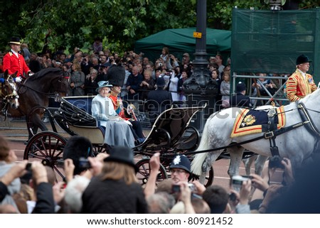 LONDON - JUNE 11: The Queen Elizabeth II & Prince Philip leaves Trooping the Color ceremony in London on June 11, 2011. Ceremony is performed by regiments on occasion of the Queen's Official Birthday - stock photo