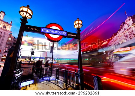 LONDON - JUNE 25: Underground sign, red bus in motion on Piccadilly Circus at night are major symbols, icons of the city on June 25, 2015 in London, UK. - stock photo