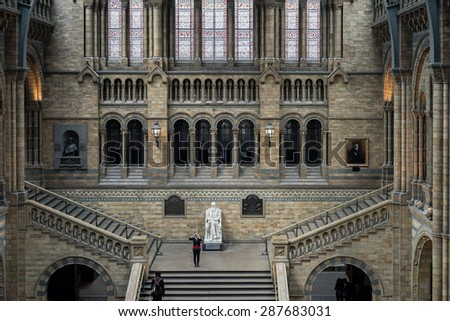 LONDON - JUNE 10 : Woman taking a photograph in the Natural History Museum in London on June 10, 2015. Unidentified people - stock photo
