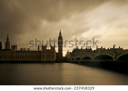 London - Long exposure of The Houses of Parliament, the Big Ben and Westminster Bridge in London under thick dark clouds - stock photo