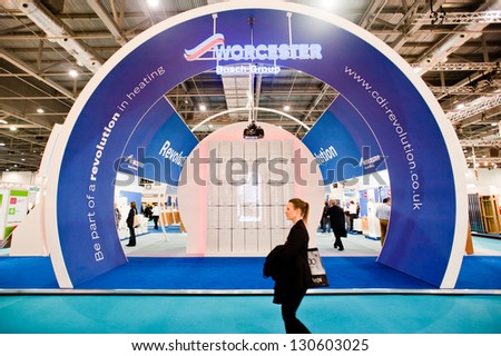 LONDON - MAR 6: a visitor walks by the Worcester stand during Ecobuild 2013 at Excel in London, UK on March 6, 2013. It is the world's biggest event for sustainable design and the built environment. - stock photo