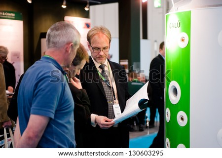 LONDON - MAR 6: an exhibitor shows a product brochure to potential customers during Ecobuild 2013 at Excel in London, UK on March 6, 2013. - stock photo