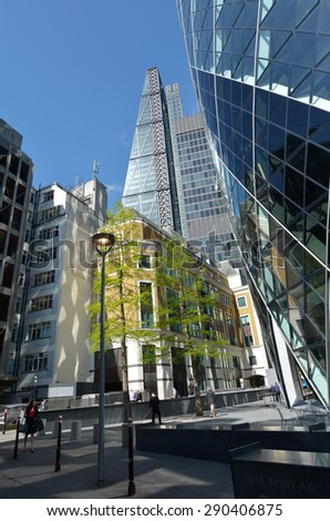 LONDON - MAR 18 2015:Business people under 122 Leadenhall Street tower and 30 St Mary Axe faced in City of London,UK. Both tall office buildings recently build in the City of London financial district