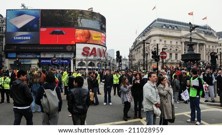 LONDON - MAR 26: Bystanders gather at Piccadilly Circus as police close roads in response to a large anti cuts rally on Mar 26, 2011 in London, UK. An estimated 250,000 protesters joined the rally. - stock photo