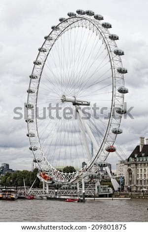 LONDON - MAR 16: The London Eye Ferris wheel pictured on March 16th, 2014, in London, UK. It is the tallest Ferris wheel in Europe, and the most popular paid tourist attraction in the United Kingdom. - stock photo