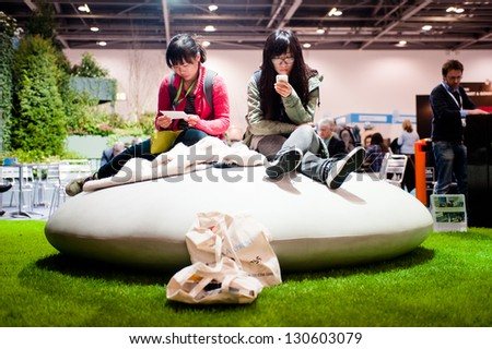 LONDON - MAR 6: visitors take a rest during Ecobuild 2013 at Excel in London, UK on March 6, 2013. Ecobuild is the world's biggest event for sustainable design, construction and the built environment. - stock photo