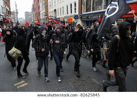 LONDON - MARCH 26: A breakaway group of anarchist protesters march through the streets of the British capital during a large anti-cuts rally 26 March 2011 in London, UK. - stock photo