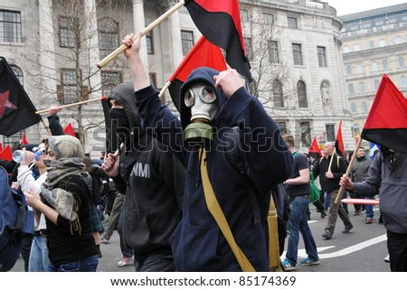 LONDON - MARCH 26: A breakaway group of anarchist protesters march through the streets of the British capital during a large anti-cuts rally March 26, 2011 in London, UK. - stock photo