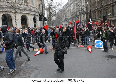 LONDON - MARCH 26: A breakaway group of anarchist protesters march through the streets of the British capital during a large TUC organised anti-cuts rally on March 26, 2011 in London, UK. - stock photo