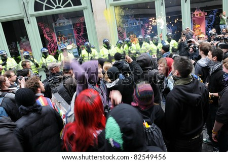 LONDON - MARCH 26: A breakaway group of anti-cuts protesters confront police and occupy Fortnum and Mason on Piccadilly during a large TUC organised rally on March 26, 2011 in London, UK. - stock photo