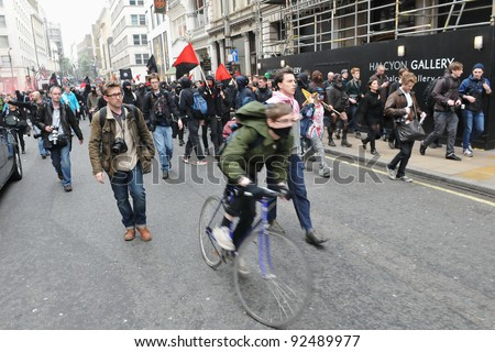 LONDON - MARCH 26: A breakaway group of protesters and journalists walk through the streets of the British capital during a large anti-cuts rally 26 March 2011 in London, UK. - stock photo