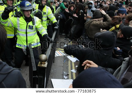LONDON - MARCH 26: A breakaway group of protesters clash with police on Piccadilly Street during a large anti-public sectors spending cuts rally organized by the TUC on March 26, 2011 in London, UK. - stock photo