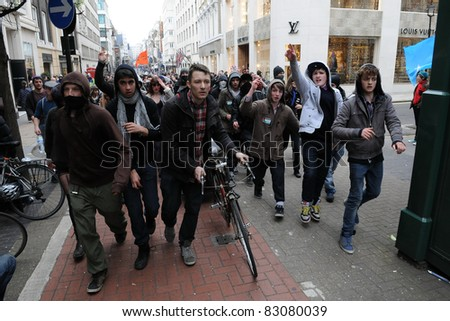 LONDON - MARCH 26: A breakaway group of protesters march through central London their during a large TUC organised anti-cuts rally on March 26, 2011 in London, UK. - stock photo
