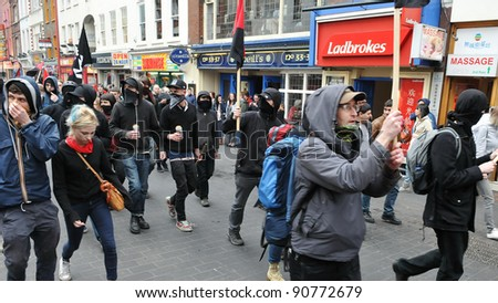 LONDON - MARCH 26: A breakaway group of protesters march through the streets of the British capital during a large anti-cuts rally on 26 March 2011 in London, UK. - stock photo