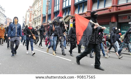 LONDON - MARCH 26: A breakaway group of protesters march through the streets of the British capital during a large anti-cuts rally on March 26, 2011 in London, UK. - stock photo