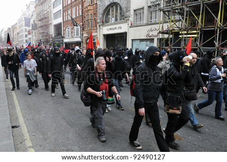 LONDON - MARCH 26: A breakaway group of protesters march through the streets of the British capital during a large anti-cuts rally 26 March 2011 in London, UK. - stock photo