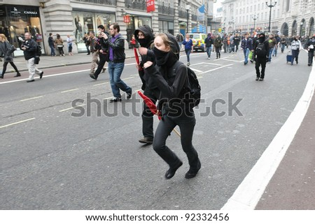 LONDON - MARCH 26: A breakaway group of protesters run along Regent Street during a large anti-cuts rally on March 26, 2011 in London, UK. - stock photo