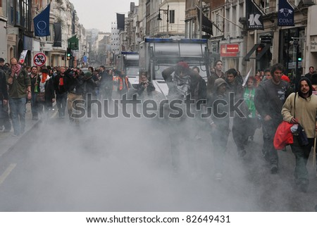 LONDON - MARCH 26: A breakaway group of protesters set off a smoke bomb in a central London street during a large anti-cuts rally on March 26, 2011 in London, UK. - stock photo