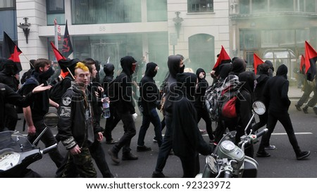 LONDON - MARCH 26: A breakaway group protesters march through the streets of the British capital during a large anti-cuts rally on March 26, 2011 in London, UK. - stock photo