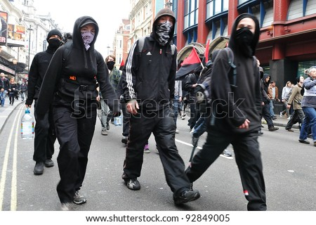 LONDON - MARCH 26: A breakaway group protesters march through the streets of the British capital during a large austerity rally on March 26, 2011 in London, UK. - stock photo