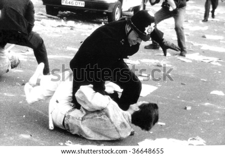 LONDON-MARCH 31: A British police officer grapples with a protester during the Poll Tax Riots on March 31, 1990 in Trafalgar Square, London. - stock photo