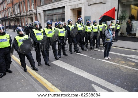 LONDON - MARCH 26: A masked anarchist protests as riot police form a road block during a 250,000 strong anti-cuts rally organised by the TUC March 26, 2011 in London, UK.