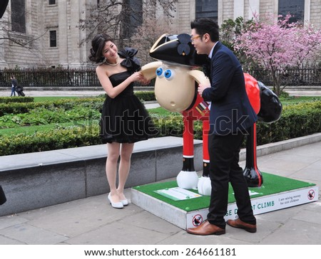 LONDON - MARCH 28, 2015. Aardman's Shaun the Sheep characters appear across the city before auctioning for a children's charity; visitors admire one near St Paul's Cathedral, London, UK. - stock photo