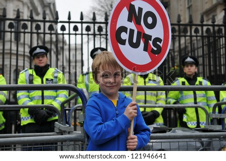 LONDON - MARCH 26: An unidentified child protests outside Downing Street during a large TUC organised anti-cuts rally on March 26, 2011 in London, UK. - stock photo