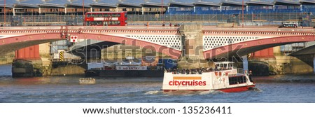 LONDON- MARCH 05: City Cruises tour boat, serving Westminster, London Eye, Greenwich piers everyday, sails on the Thames River, longest river in England with 346 km long on March 5, 2013 in London, UK - stock photo