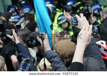 LONDON - MARCH 26: Journalists jostle for position to photograph protesters clashing with riot police during a large austerity rally on March 26, 2011 in London, UK. - stock photo