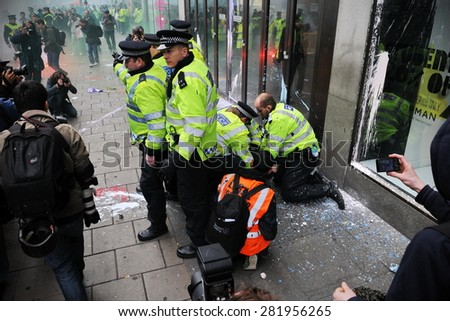 LONDON - MARCH 26: Police arrest a protester during a large anti austerity rally on March 26, 2011 in London, UK. Protesters clashed with police repeatedly with dozens of arrests. - stock photo