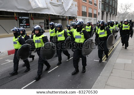 LONDON - MARCH 26: Police in riot gear advance through central London during a large anti-cuts rally on March 26, 2011 in London, UK. - stock photo