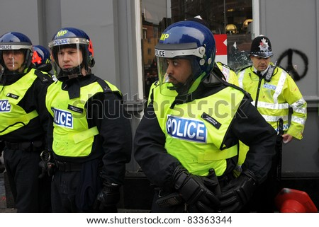 LONDON - MARCH 26: Police in riot gear on standby in central London during violent anti-cuts protests on March 26, 2011 in London, UK. - stock photo